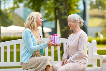family, holidays and people concept - happy smiling young daughter giving present to her senior mother sitting on park bench