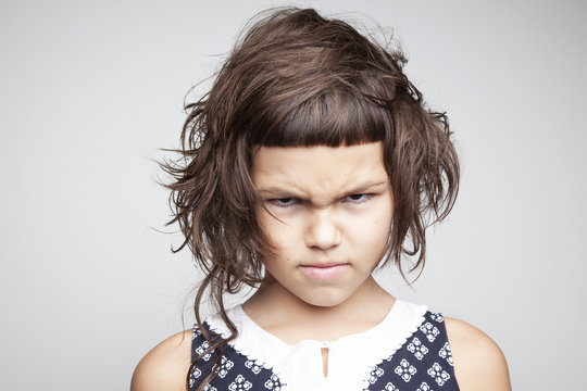 Little angry girl with stylish haircut