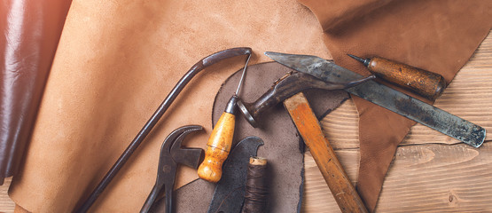 Old tools and leather at cobbler workplace. Shoemaker's work desk. Flat lay, top view. Set of leather craft tools on wooden background. Shoes maker tools. Pieces of brown leather. Shoemaker's shop.