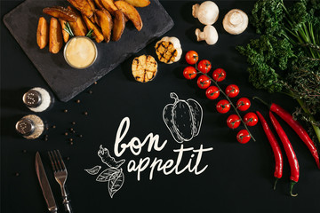 "top view of tasty baked potatoes with sauce, spices and vegetables on black with ""bon appetit"" lettering"