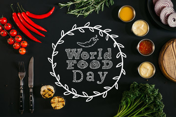 "top view of various sauces, grilled garlic, fork with knife and fresh vegetables with herbs on black background with ""world food day"" lettering"