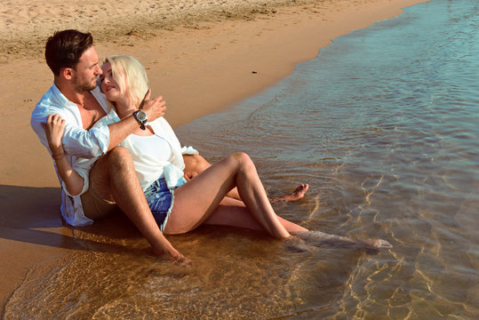 Beautiful happy couple in love lying on a beach on sand in a white shirts are in love smiling. Handsome bearded men and sexy blonde women in water in wet clothes having fun kissing, and laughing