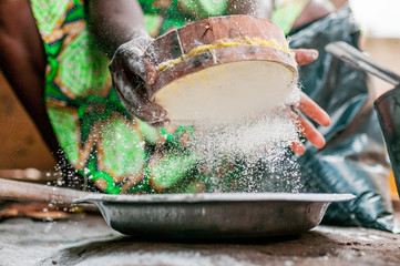 beautiful image of black woman hands searching and sifting corn white flour while cooking traditional african dish with african dress