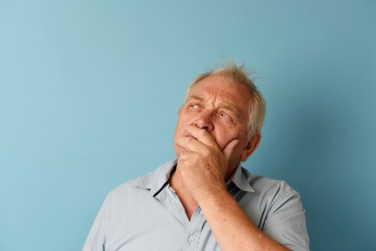 Happy mature man thinking, taken on a blue background with copy space