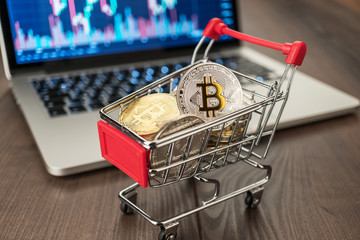 shopping trolley full of bitcoin currency with laptop showing stock market rates in the background concept on the wooden table
