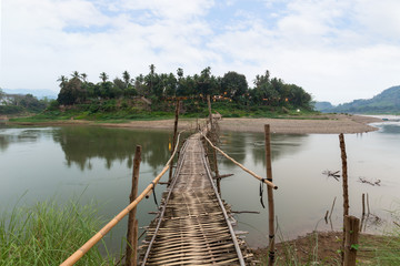 Wooden bamboo bridge over Nam Khan River at low tide viewed from the front in Luang Prabang, Laos.