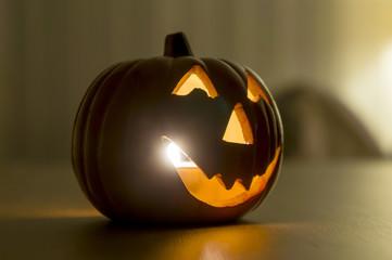 Lighted halloween pumpkin on wooden table