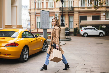 Beautiful girl in trench coat with little black cross bag holding cup of coffee to go and shopping bags in hands dreamily looking in camera while walking around cozy city street Wall mural