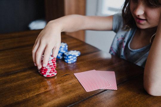 Girl playing cards at table, stacking gambling chips, close up