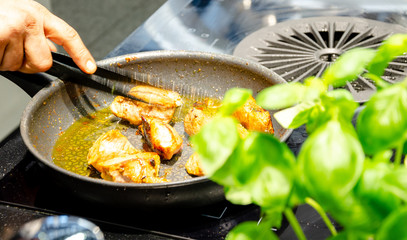 chef grabbing chicken from pan
