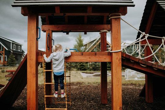 Girl climbing ladder to playground platform, rear view