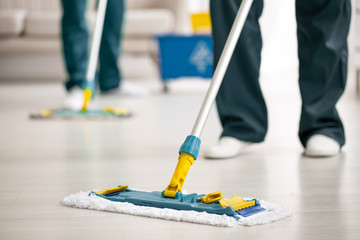 Close-up on mop on the floor holding by cleaning specialist while purifying interior