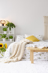 Sunny spring bedroom interior with green plants beside a bed dressed in eco cotton linen. Yellow accents. Empty white background wall. Real photo.