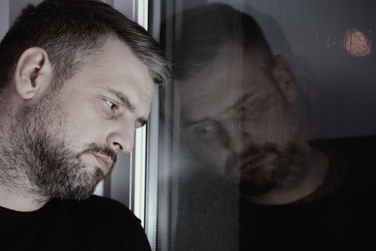 Sad man with nervous breakdown and mental disorder looking through window