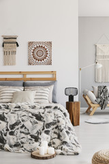 Patterned sheets on bed next to lamp on wooden stool in bedroom interior with poster. Real photo