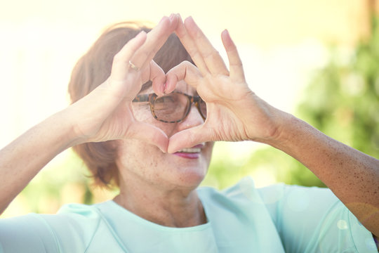 Closeup Healthy Eyes And Vision. Portrait senior old Woman Holding Heart Shaped Hands Near Eyes. Showing Love Sign. Eyecare.