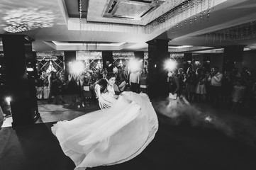 First wedding dance of newlywed. bride and groom dancing in restaurant. Wedding couple dancing in smoke. Black and white photo