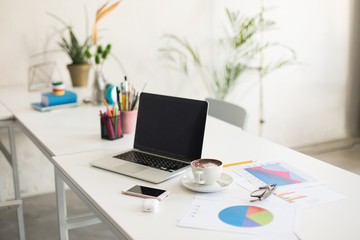 Photo of laptop and white cup of coffee on desk in modern office