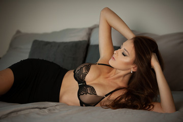Boudoire photo of a gorgeus young woman lying in bed