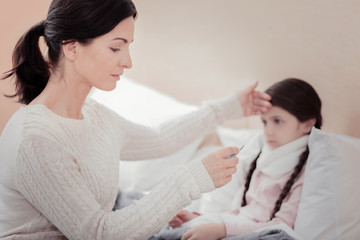 Slight illness. Close up of careful young mother using thermometer and looking at it while keeping hands on daughters forehead