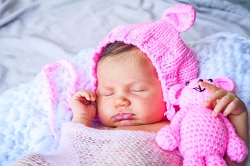 Cute adorable sweet newborn infant girl in a pink funny cap with ears sleeping. Strong and serene newborn baby sleep concept image.