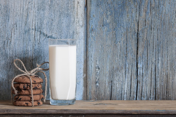 Chocolate chip cookies and a glass of milk on a wooden table