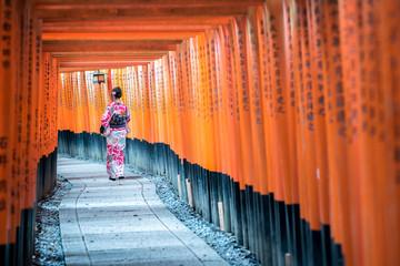 KYOTO, JAPAN - 2016  November 21 : geishas wearing traditional japanese kimono among red wooden Tori Gate at Fushimi Inari Shrine in Kyoto, Japan. Fushimi Inari Shrine one of famous landmarks. Wall mural