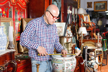 Experienced appraiser of antiques shop measuring antique vase while determining value
