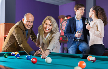 Relaxed cheerful positive smiling people playing billiard and darts