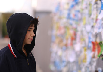 teenager boy looking through announcement advertising on concrete wall