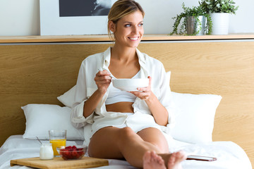 Beautiful young woman having breakfast and looking outside, lying in the bed.