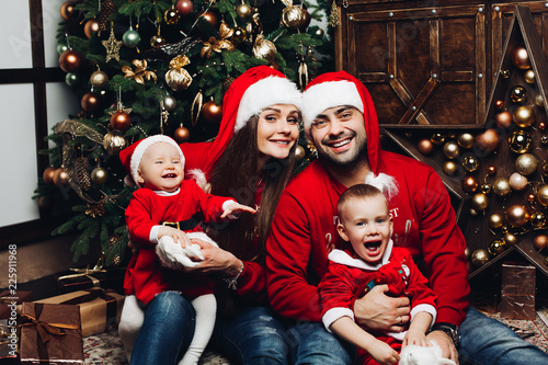 3d78747fa Portrait of beautiful cheerful family in red hats and sweaters ...