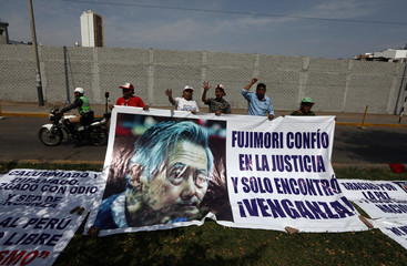Supporters of former President Alberto Fujimori hold a banner with a picture of him outside the Centenario hospital where he is hospitalised, after a judge annulled a presidential pardon and ordered his immediate capture and return to prison, in Lima