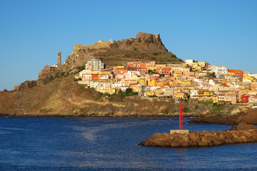 The picturesque town of Castelsardo with colourful houses, a bell tower and a fortified castle, surrounded by the Mediterranean Sea and glowing in the evening sun, Sardinia, Italy