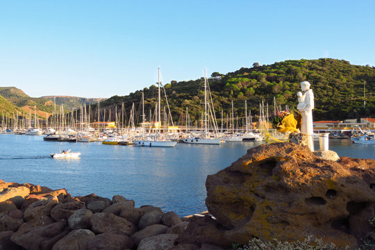Patron saint looking out over the yachts moored at the harbor in the bay of Castelsardo at sunset, Sardinia, Italy
