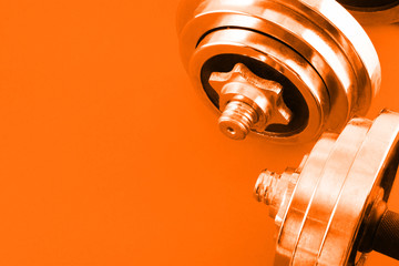 Bright real working dumbbells from several parts on a orange background.