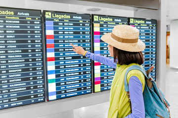 Young asian woman with backpack in international airport looking at the flight information timetables board