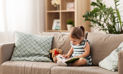 childhood and people concept - little girl sitting on sofa reading book and toy teddy bear at home