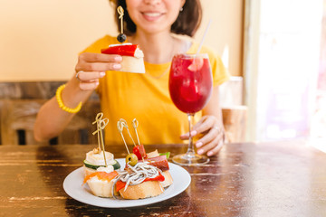 Traveler woman drink sangria and eating tapas in spanish cafe