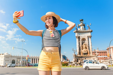 Happy woman tourist making selfie photo at the Spain Square in Barcelona city. Travel and summer vacation in Europe