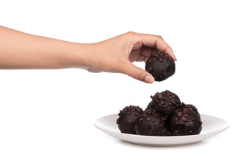 hand holding chocolate ball on plate isolated on a white background