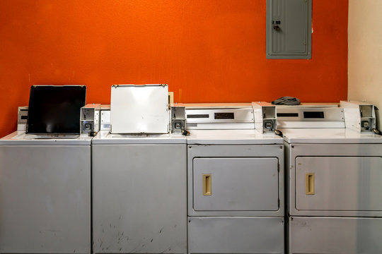 coin washing machine laundry in front of an orange wall