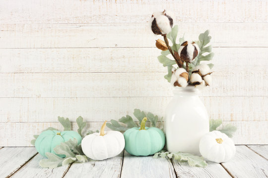 Thanksgiving scene with white and teal pumpkins against a white wood background