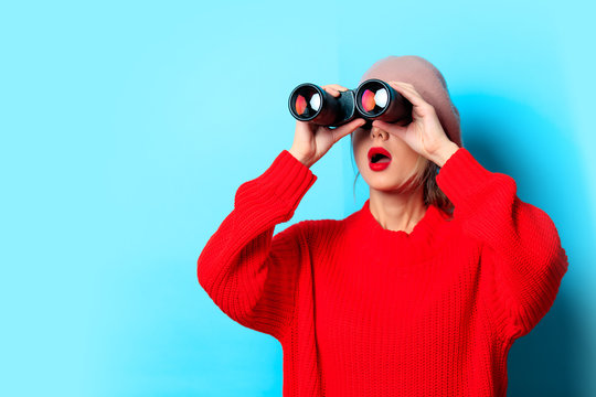 Portrait of a young girl in red sweater with binocular on blue background