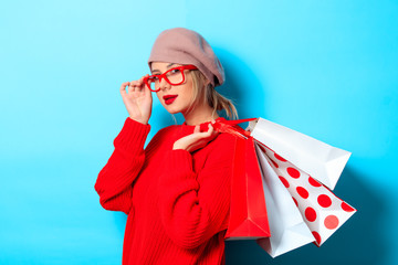 Portrait of a young girl in red sweater with shopping bags on blue background