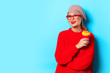Portrait of a young girl in red sweater with cup of coffee on blue background