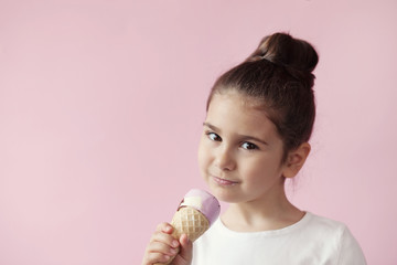 Happy little girl eating ice-cream in a crispy cone. Space for text.