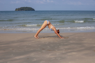Young woman yoga on sand beach. Tropical seaside vacation activity. Young girl fitness and stretch.