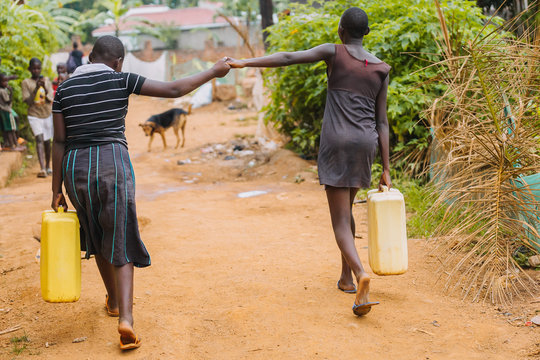 women carrying water cans in Uagnda, Africa