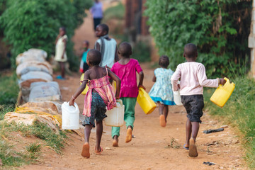 In de dag Afrika children carrying water cans in Uganda, Africa